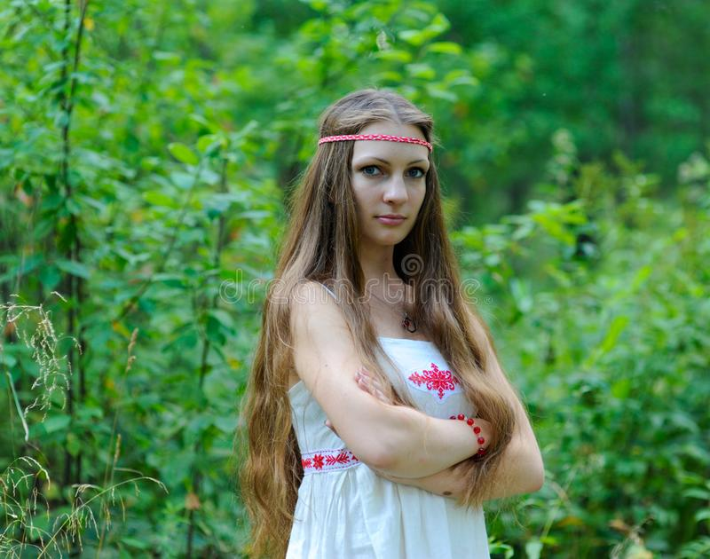 Portrait of a young beautiful Slavic girl with long hair and a Slavic ethnic dress on a background of green grass stock images