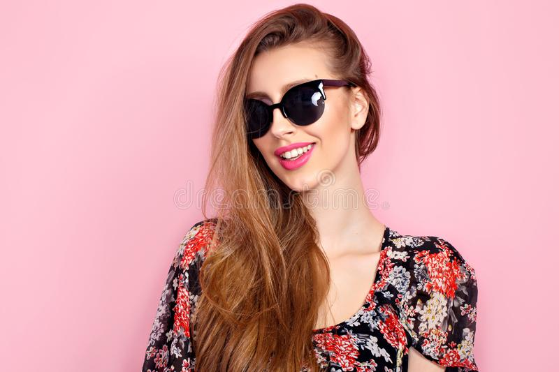 Portrait of young beautiful slim woman in sexy dress with sensual lips in studio wearing sunglasses. smiling and posing royalty free stock image
