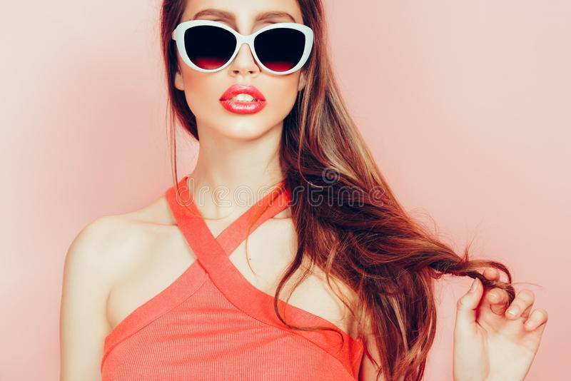 Portrait of young beautiful slim woman in sexy dress with sensual lips in studio wearing sunglasses. smiling and posing royalty free stock photo