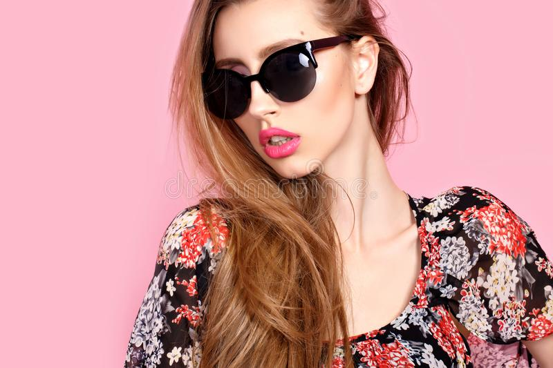Portrait of young beautiful slim woman in sexy dress with sensual lips in studio wearing sunglasses. smiling and posing stock photography