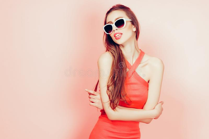 Portrait of young beautiful slim woman in sexy dress with sensual lips in studio wearing sunglasses. smiling and posing stock images