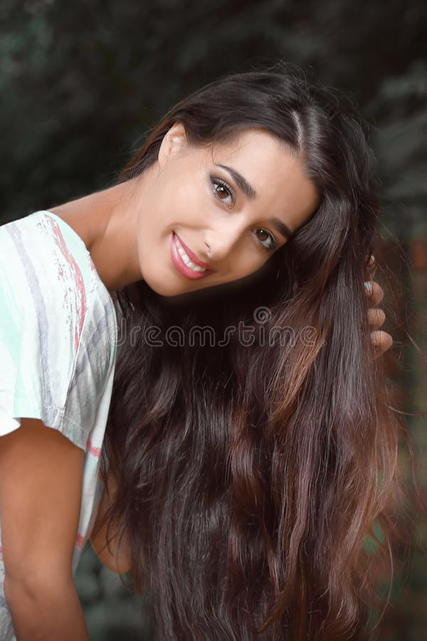 Portrait of young beautiful smiling female with long dark hair looking into camera outdoor stock photos