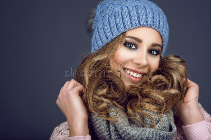 Portrait of young beautiful smiling girl with professional make up and curly hair coming out of her blue knitted hat stock photo