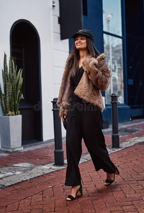 Smiling fashion young woman walking in the city stock images