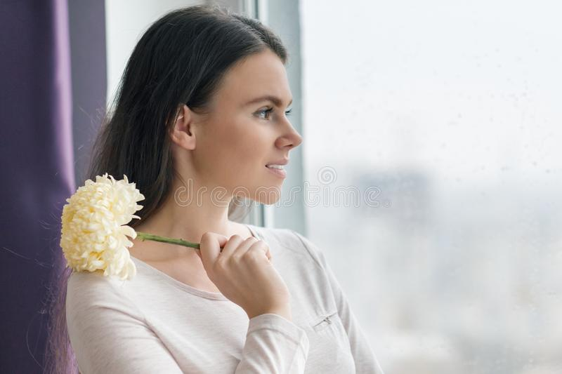 Portrait of young beautiful smiling woman with natural makeup, with large pale yellow flower in her hands, girl looking out the stock photography