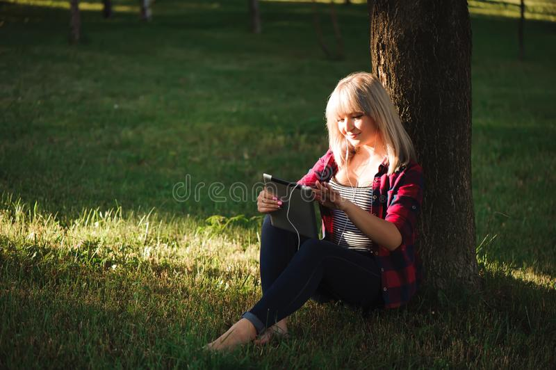 Portrait of young beautiful smiling woman with tablet pc, outdoors royalty free stock photo