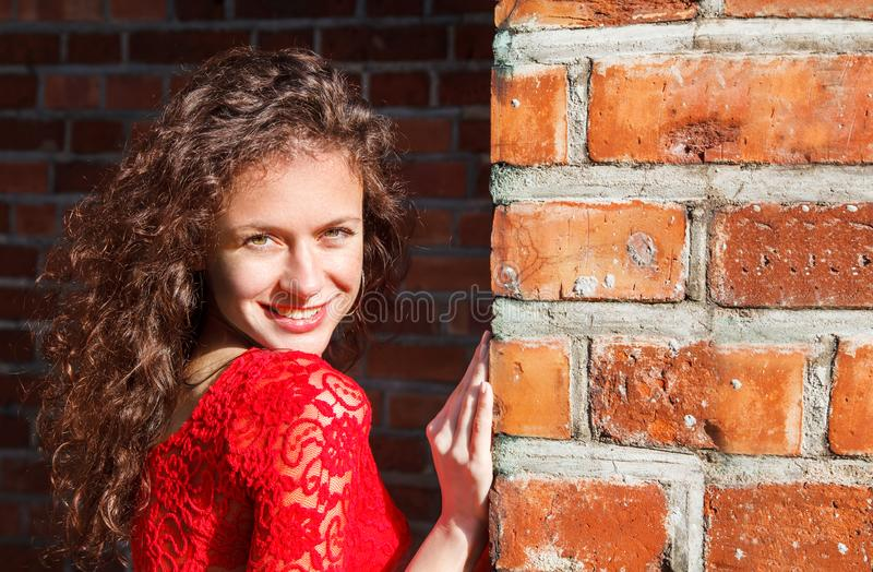Portrait of a young beautiful spanish girl in red dress near the brick wall stock photography