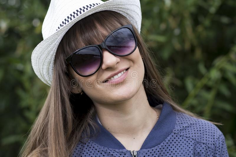 Portrait of young beautiful teenage girl in hat and sunglasses in summer park. Happy smiling cute girl on green nature background. stock images