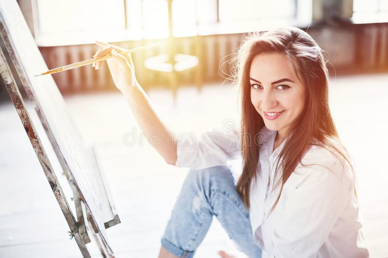 Young beautiful woman artist painting on canvas at workspace in sunlight. Portrait of a young beautiful woman artist painting on canvas at workspace in sunlight royalty free stock photo