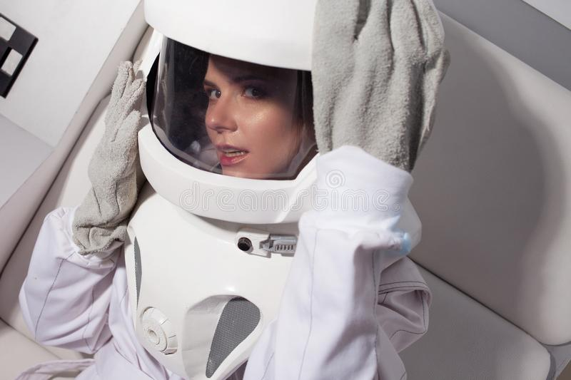 Portrait of a young beautiful woman astronaut, close-up. The woman in the suit screams stock photography