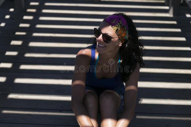 Portrait of a young beautiful woman at the beach at sunset. Summer, fun and lifestyle. Stripes shadows stock photo