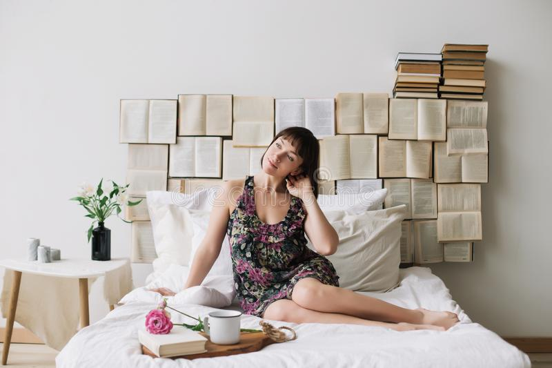 Portrait of a young beautiful woman in bed at home. Beautiful young brunette in the bedroom. Good morning. Lifestyle. Portrait of a young beautiful woman with stock image