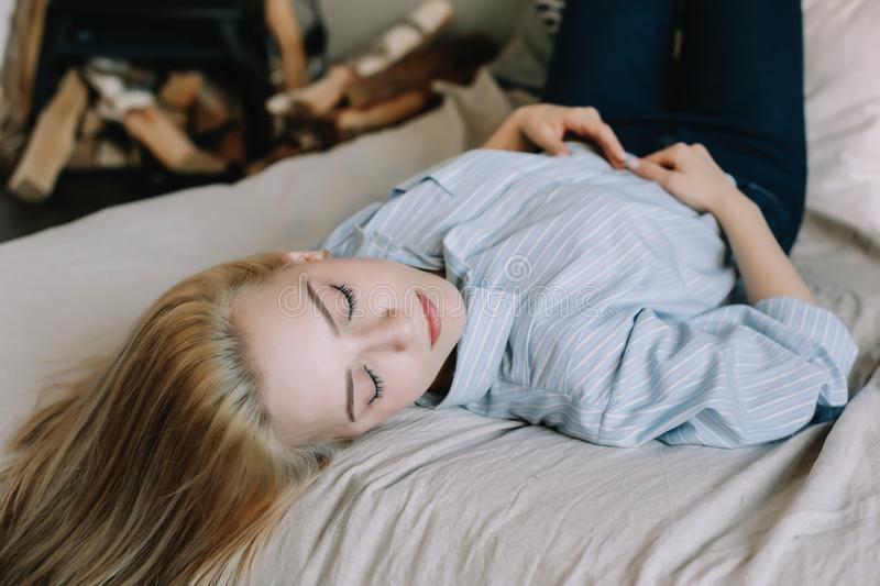 Portrait of a young beautiful woman in bed in the morning at home. Blonde girl in scandinavian interior. Good morning. Lifestyle. Portrait of a young beautiful royalty free stock photo