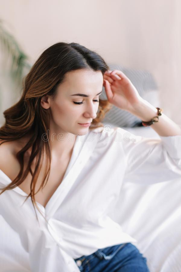 Portrait of a young beautiful woman in bed in the morning at home. Beautiful brunette in the bedroom. Good morning. Lifestyle. Portrait of a young beautiful royalty free stock photos