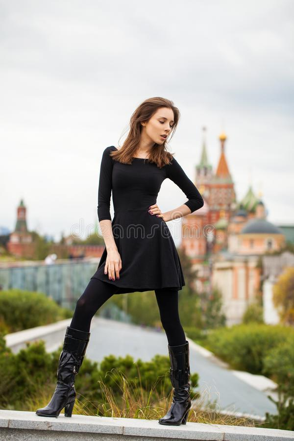 Portrait of young beautiful woman in black dress posing in autumn park on a background of Red Square in Moscow stock photography