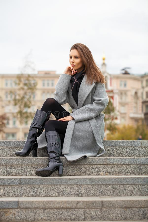Portrait of a young beautiful woman in a black dress sitting on the stone steps in the autumn park royalty free stock images
