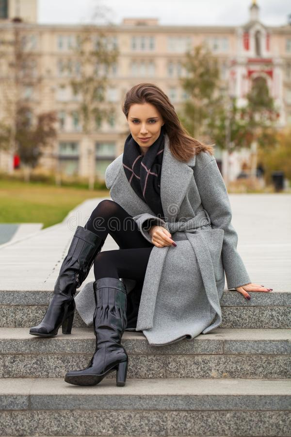 Portrait of a young beautiful woman in a black dress sitting on the stone steps in the autumn park stock photos