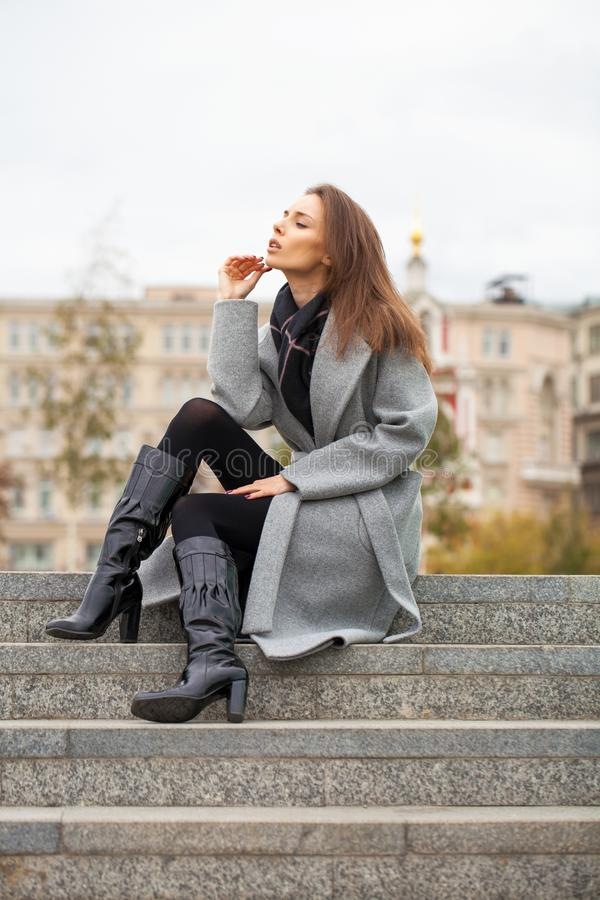 Portrait of a young beautiful woman in a black dress sitting on the stone steps in the autumn park royalty free stock image