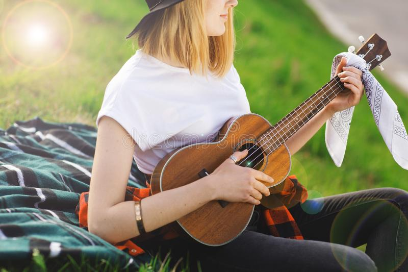 Portrait of a young beautiful woman in a black hat. Girl sitting on the grass and playing guitar.  royalty free stock photos