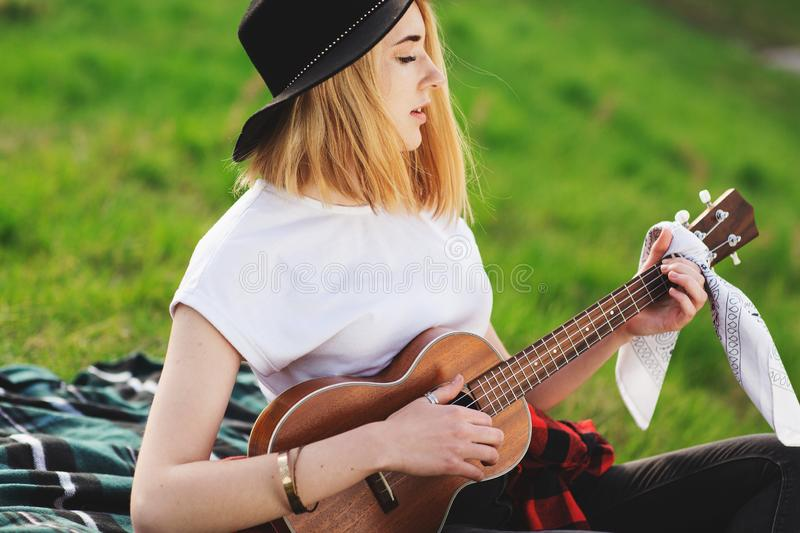 Portrait of a young beautiful woman in a black hat. Girl sitting on the grass and playing guitar stock photos