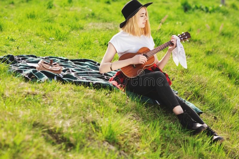 Portrait of a young beautiful woman in a black hat. Girl sitting on the grass and playing guitar.  stock photography