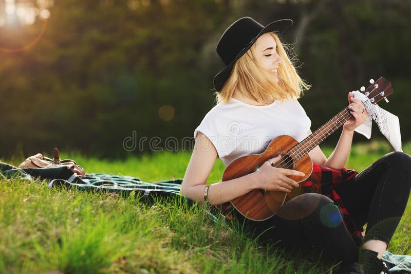 Portrait of a young beautiful woman in a black hat. Girl sitting on the grass and playing guitar.  stock images