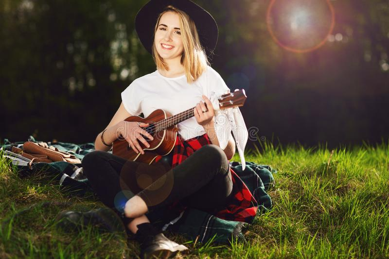 Portrait of a young beautiful woman in a black hat. Girl sitting on the grass and playing guitar.  stock photo