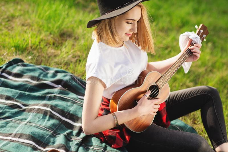 Portrait of a young beautiful woman in a black hat. Girl sitting on the grass and playing guitar.  royalty free stock image