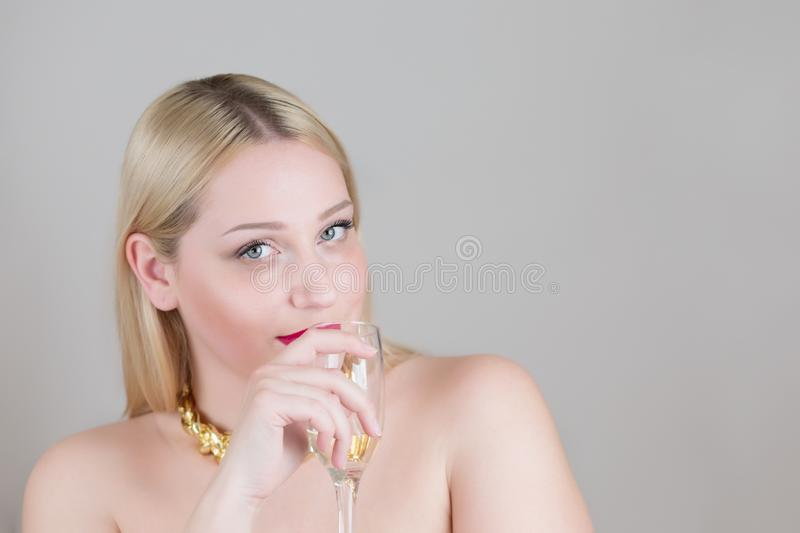 Portrait of a young beautiful woman blonde holding a glass of champagne. royalty free stock images