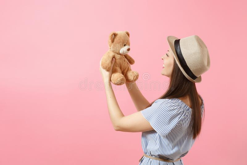 Portrait of young beautiful woman in blue dress, summer straw hat holding teddy bear plush toy isolated on pink royalty free stock image