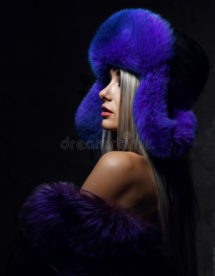 Portrait of young beautiful woman in blue purple fashion arctic fox winter fur ear flap hat. Portrait of young beautiful woman in blue purple fashion arctic fox royalty free stock photo