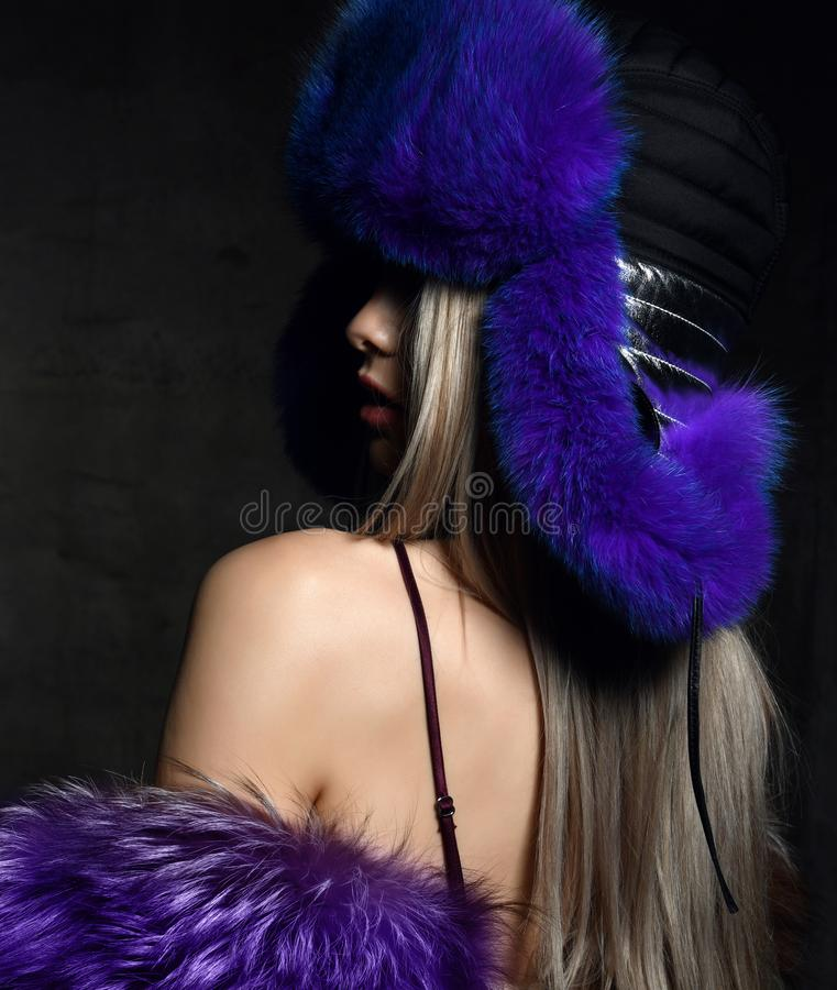 Portrait of young beautiful woman in blue purple fashion arctic fox winter fur ear flap hat. Portrait of young beautiful woman in blue purple fashion arctic fox royalty free stock images