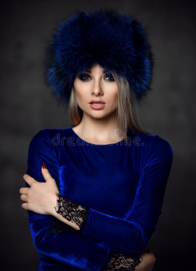 Portrait of young beautiful woman in blue purple fashion arctic fox winter fur ear flap hat. Portrait of young beautiful woman in blue purple fashion arctic fox stock photo