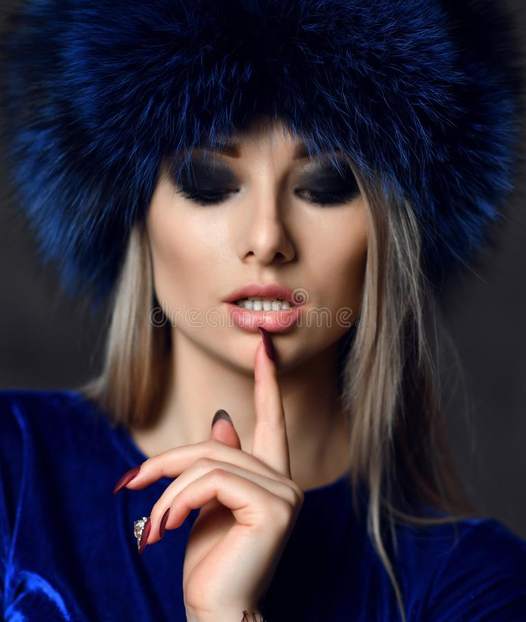 Portrait of young beautiful woman in blue purple fashion arctic fox winter fur ear flap hat. Portrait of young beautiful woman in blue purple fashion arctic fox stock photography