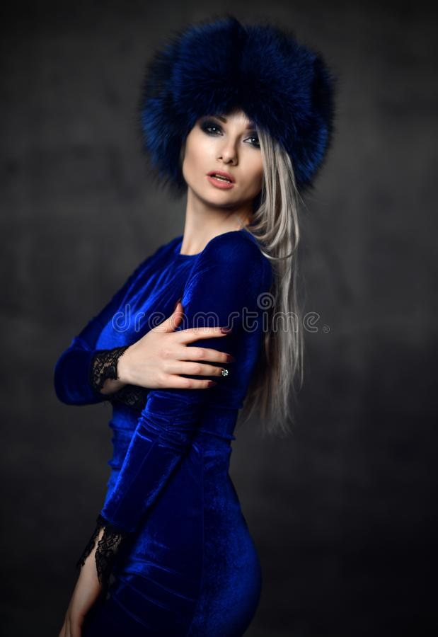 Portrait of young beautiful woman in blue purple fashion arctic fox winter fur ear flap hat. Portrait of young beautiful woman in blue purple fashion arctic fox stock photos