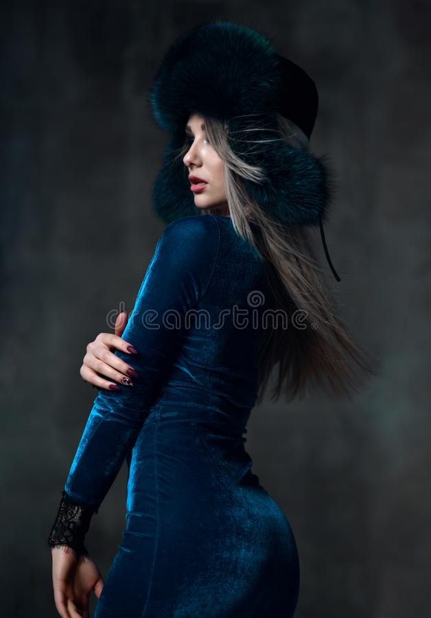 Portrait of young beautiful woman in blue purple fashion arctic fox winter fur ear flap hat. Portrait of young beautiful woman in blue purple fashion arctic fox stock images