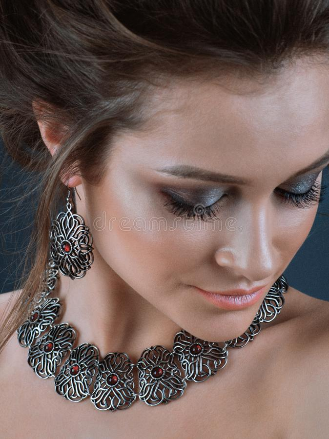 Portrait of young beautiful woman with brown hair fresh skin wearing accessories and jewelry isolated over dark blue background stock image