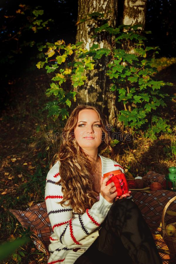 Portrait of young beautiful woman with cup of coffee in autumn park.Fall concept - autumn Brunette woman drinking coffee royalty free stock photos