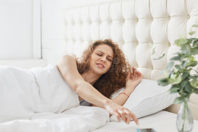 Portrait of young beautiful woman with curly hair being in her bed in morning, stretching her arm to switch off alarm clock on stock photos