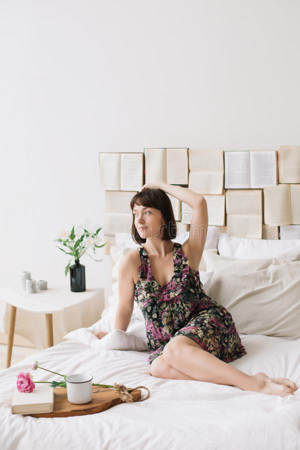 Portrait of a young beautiful woman in bed at home. Beautiful young brunette in the bedroom. Good morning. Lifestyle. Portrait of a young beautiful woman with royalty free stock photos