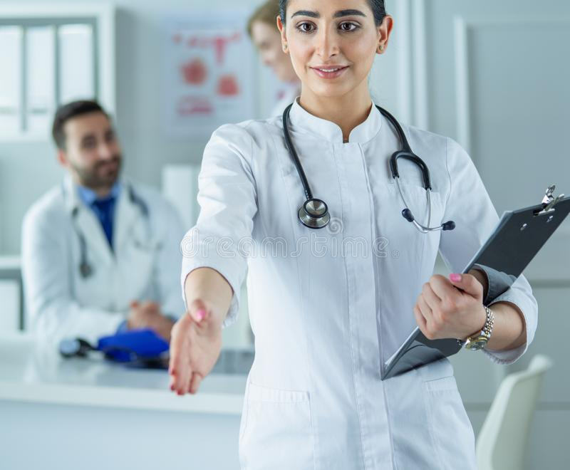 Portrait of young beautiful woman doctor giving handshake royalty free stock photo