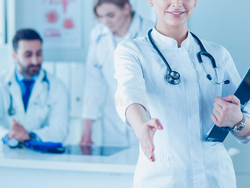 Portrait of young beautiful woman doctor giving handshake stock photography