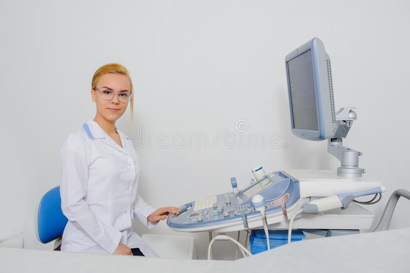 Doctor working at ultrasound diagnostic machine. Portrait of young beautiful woman doctor working at ultrasound diagnostic machine usg stock images