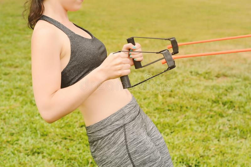 Portrait of young beautiful woman doing exercise at park stock images