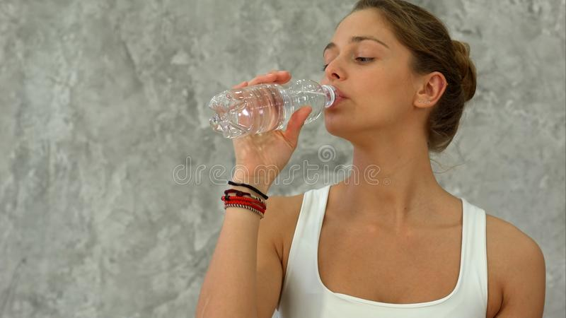 Portrait of young beautiful woman drinking water after yoga class royalty free stock image