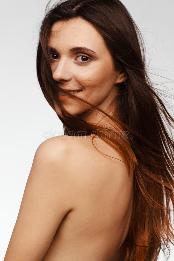 Portrait of a young beautiful woman with hair flying from the wind and bare shoulders royalty free stock photography