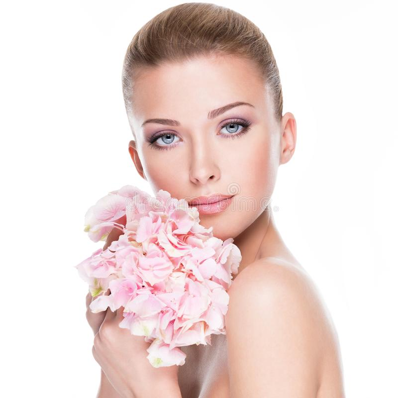 Portrait of young beautiful woman with flowers at face stock photo