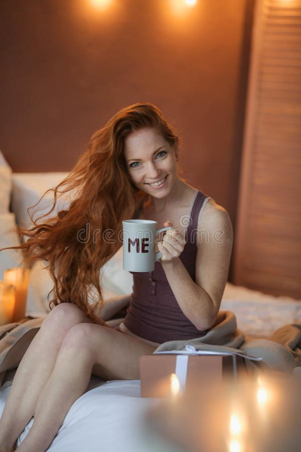 Portrait of young beautiful woman her hands holding cup of coffee morning cold winter time in her white bedroom. Happy royalty free stock photography