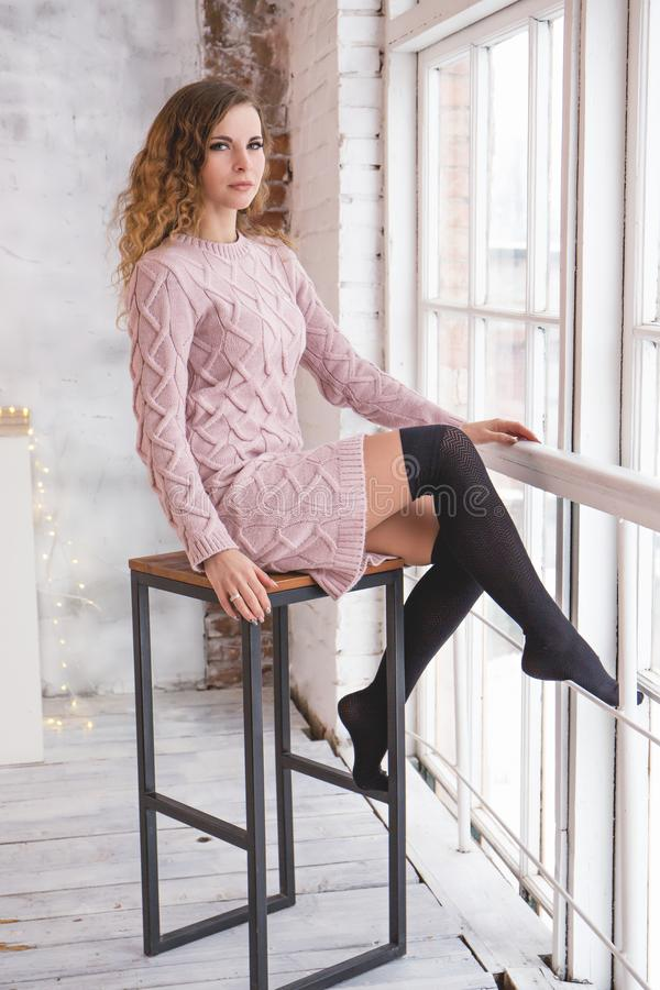 Young beautiful woman in a knitted dress by the window stock image