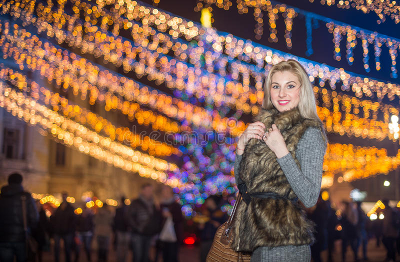 Portrait of young beautiful woman with long fair hair outdoor in cold winter evening. Beautiful blonde girl in winter clothes stock images